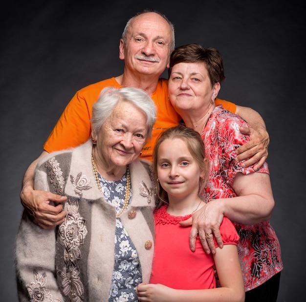 Счастливая семья из нескольких поколений на серой стене