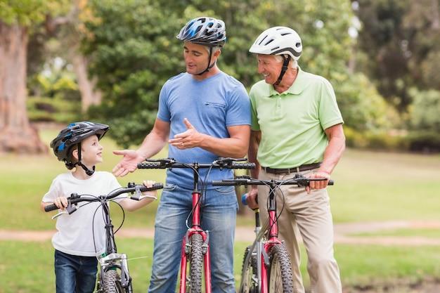 公園で自転車に乗っているハッピー・マルチ世代の家族