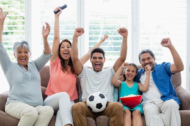 Счастливая многопоколенная семья смотрит футбольный матч по телевизору в гостиной