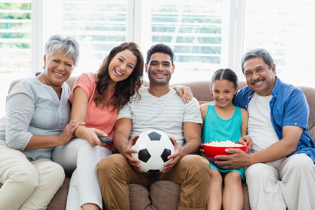 Happy multi-generation family watching soccer match on television in living room