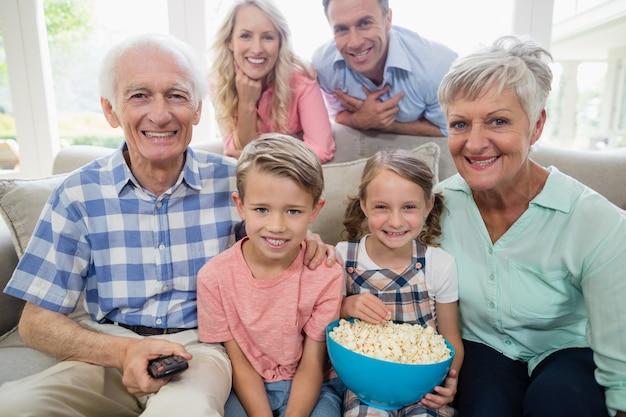 リビングルームでテレビを見て幸せな多世代家族