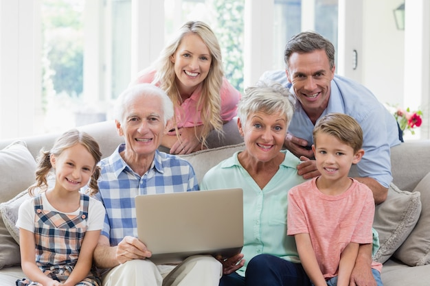 リビングルームにラップトップを持つ幸せな多世代家族
