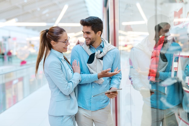Счастливая многокультурная пара оделась элегантно стоя перед витриной и искала что-нибудь купить.