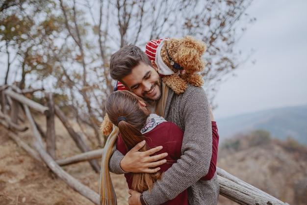 Счастливая многокультурная влюбленная пара одела случайные объятия в природе на осень. человек, имеющий свою собаку на плечи.