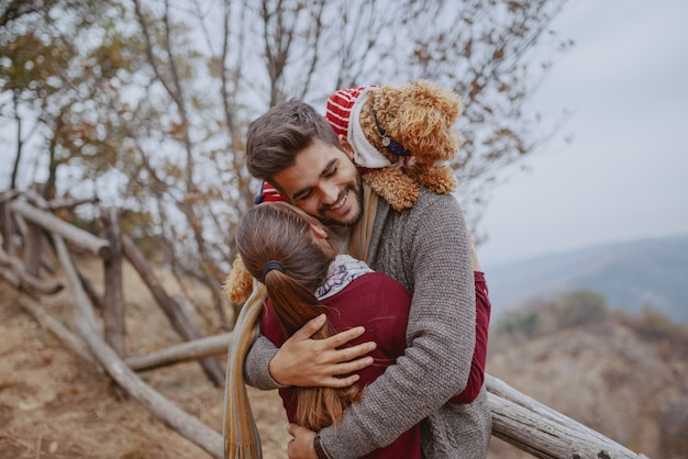 Happy multicultural couple in love dressed casual hugging in nature at autumn. man having their dog on shoulders.