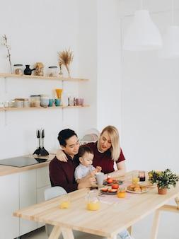 Счастливая многокультурная семья. азиатский папа и его кавказская белокурая жена завтракают с их красивым сыном на кухне.