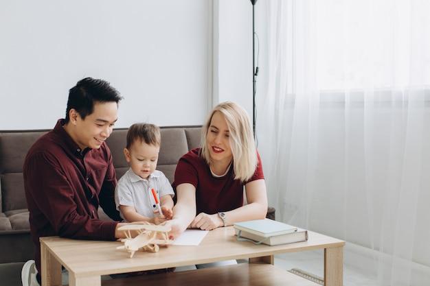 幸せな多文化家族。アジア人男性と白人女性が息子と一緒に描いています。