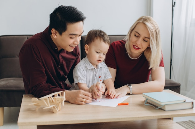 Happy multicultural family. asian man and caucasian woman drawing with their son.