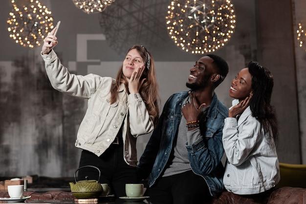 Felici amici multiculturali che prendono selfie