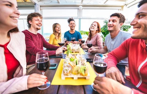 개인 홈 파티에서 펜트하우스에서 함께 와인을 마시는 행복한 다문화 사람들