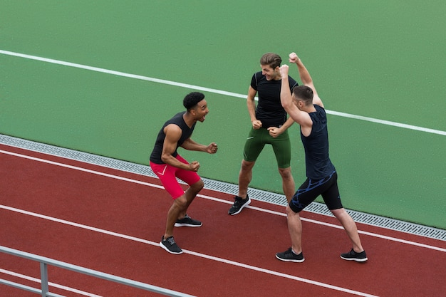 Happy multiethnic athlete team make winner gesture