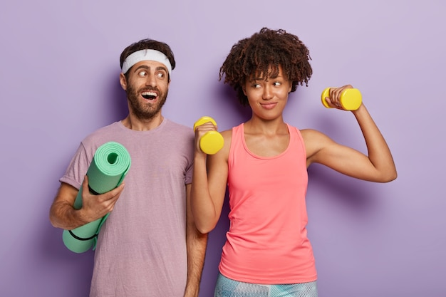 Happy multiethnic couple achieve sport success, have workout in gym with dumbbells