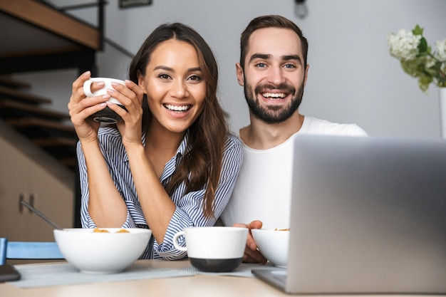 Счастливая многонациональная пара завтракает на кухне, глядя на портативный компьютер