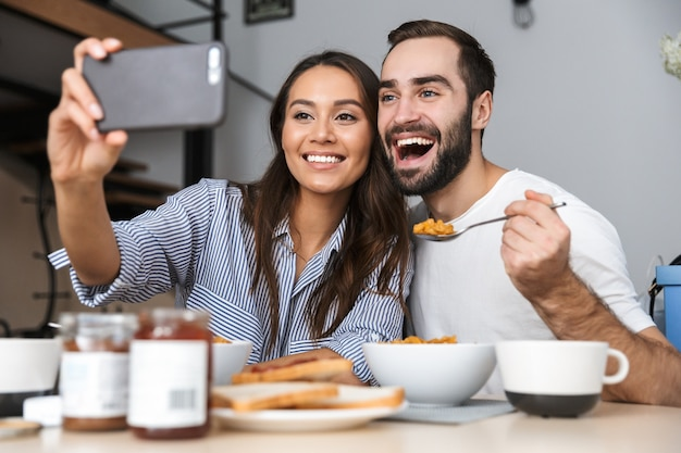 Счастливая многонациональная пара завтракает на кухне, делая селфи