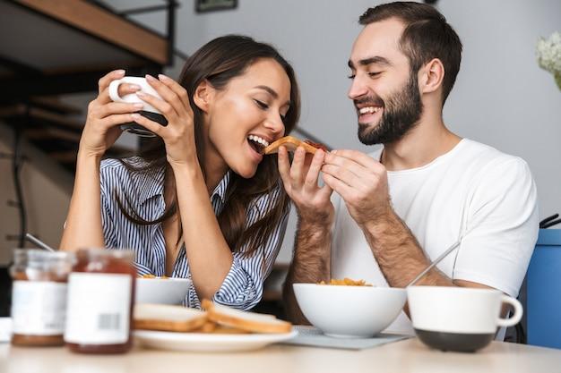Счастливая многонациональная пара завтракает на кухне