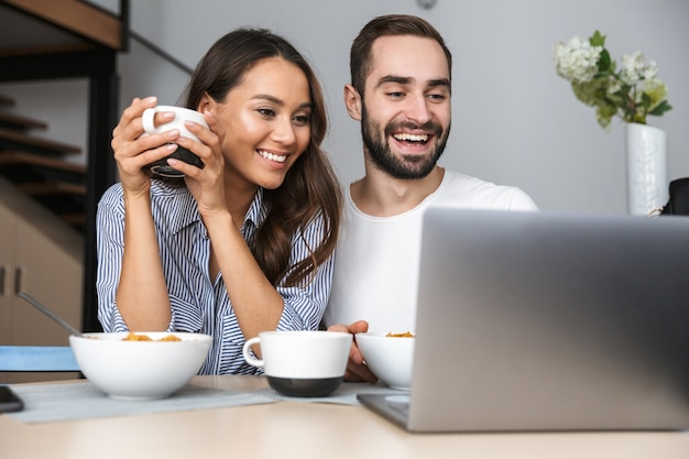 Happy multiethnic couple having breakfast at the kitchen, looking at laptop computer