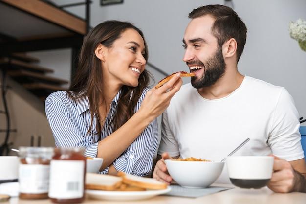 Happy multiethnic couple having breakfast at the kitchen