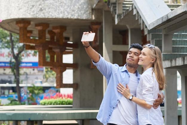 スマートフォンで抱き締めて自分撮りを愛する幸せな多民族のカップル