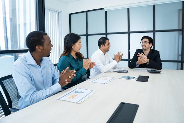 Happy multiethnic employees applauding at meeting while congratulating each other