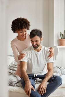 Happy multiethnic family couple look happily at pregnancy test, feel excited, celebrate good news, pose at bedroom, wears casual clothes, sit at comfortable bed during morning time. fertility concept