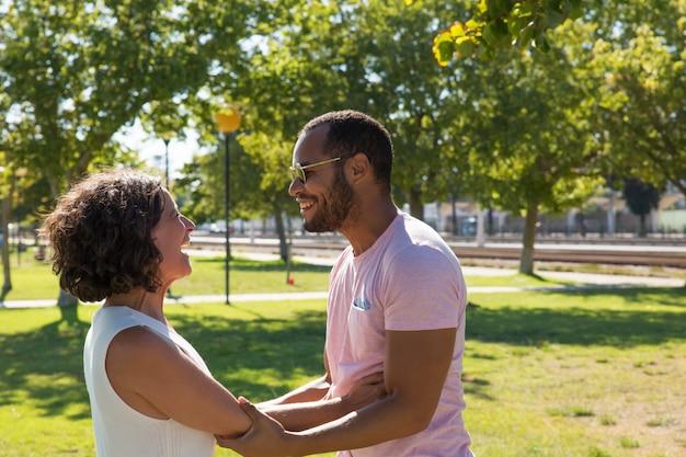 Счастливые многонациональные друзья, держась за руки в парке