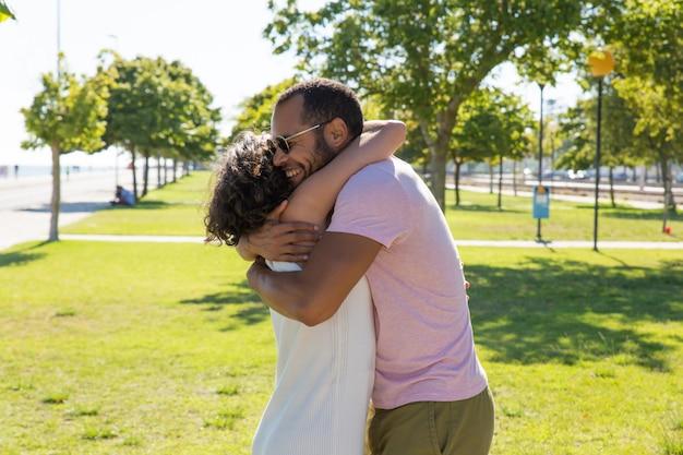 Happy multiethnic friends hugging in park