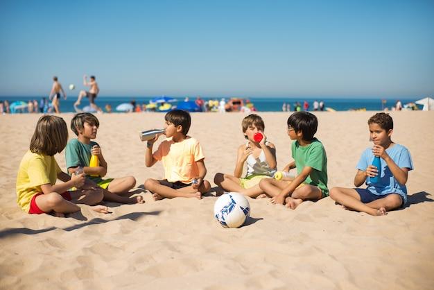 Happy multiethnic preteen boy friends on beach