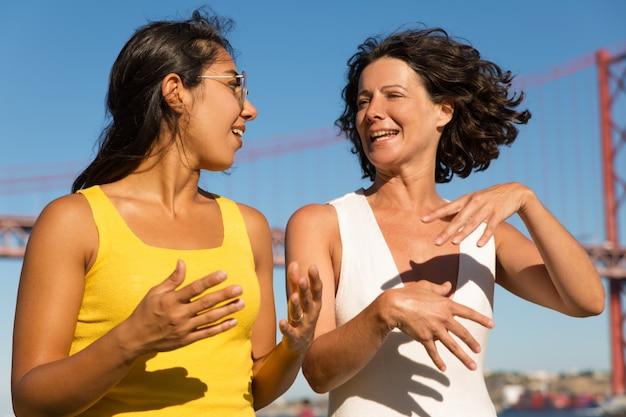 リバーサイドで歩いて幸せな多民族女性