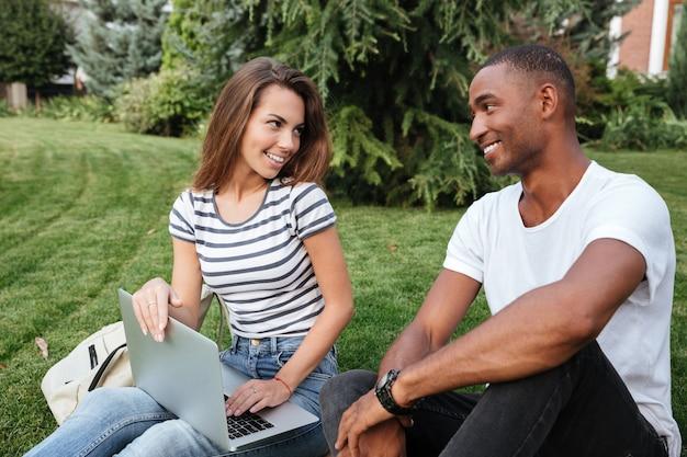 Счастливая многонациональная молодая пара сидит и использует ноутбук на лужайке на открытом воздухе