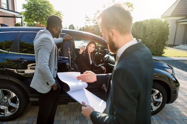 Happy multiethnical couple, african man and caucasian woman, buying the car, black crossover, woman is sitting in the car and holding car keys. young salesman holds folder with contract for sale
