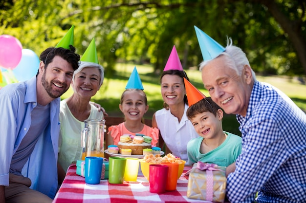 公園で誕生日パーティーを祝う幸せな多世代家族