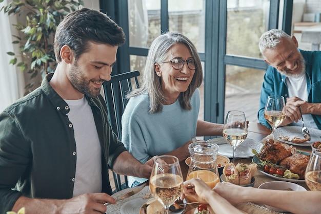 Счастливая многопоколенная семья общается и улыбается во время совместного ужина