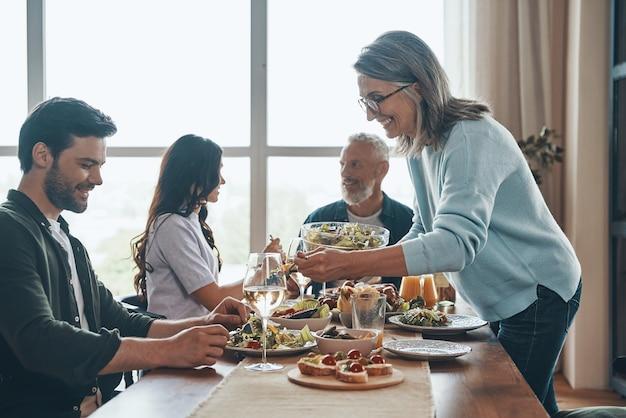 Счастливая семья из разных поколений наслаждается ужином и улыбается, сидя в современной квартире