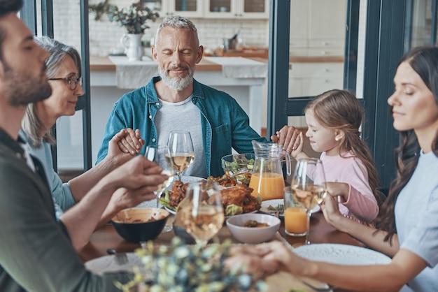 Счастливая семья из разных поколений, взявшись за руки и молившись перед ужином