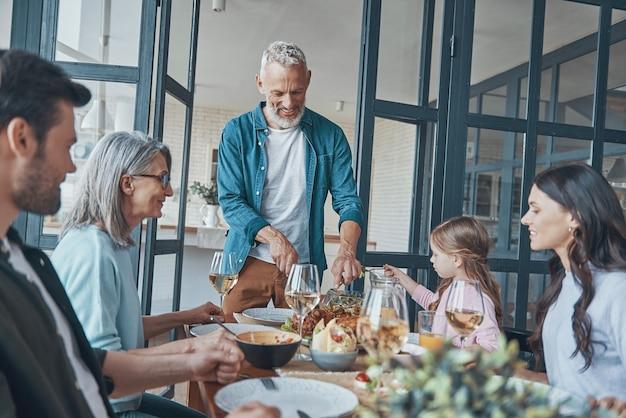 Счастливая семья из разных поколений улыбается во время совместного ужина
