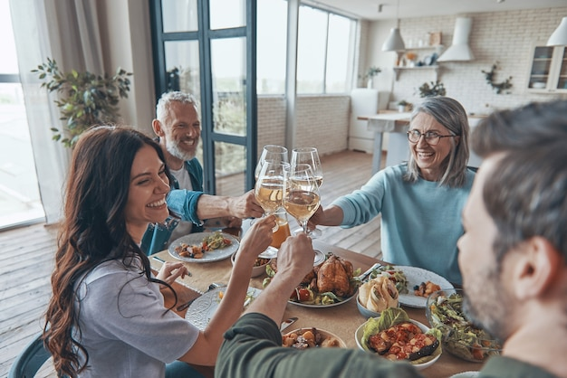 Счастливая семья из разных поколений тосты и улыбка во время совместного ужина