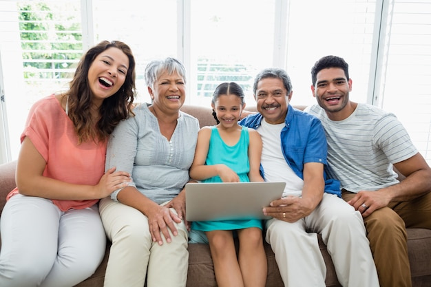 Happy multigenration family using laptop in living room at home