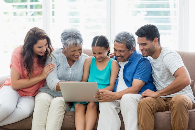 Happy multigenration family using laptop in living room