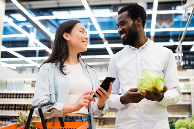 Happy multiracial couple choosing goods and looking at each other in supermarket