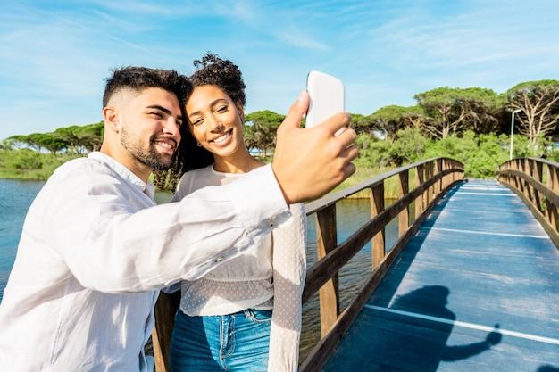 自然の休暇で自分撮りをしている木製の橋に滞在するのが大好きな幸せな多民族のカップル。スマートフォンを使用してヒスパニック系のガールフレンドと自分自身を撮影するハンサムな男。新しいテクノロジーの習慣