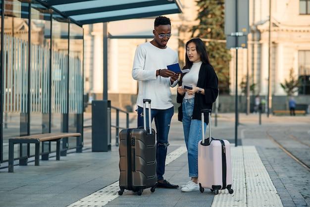 幸せな多民族のカップルは、空港近くの停留所で出発時刻をチェックする搭乗券を見てください。休暇旅行のコンセプト。