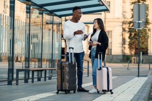 Счастливая многорасовая пара смотрит на посадочный талон, проверяя время отправления на остановке возле аэропорта.