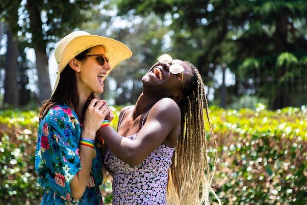 Счастливая пара многорасовых геев вместе смеются в жаркий летний день в размытом фоне. скопируйте пространство. концепция лгбт. концепция любви. летнее понятие.