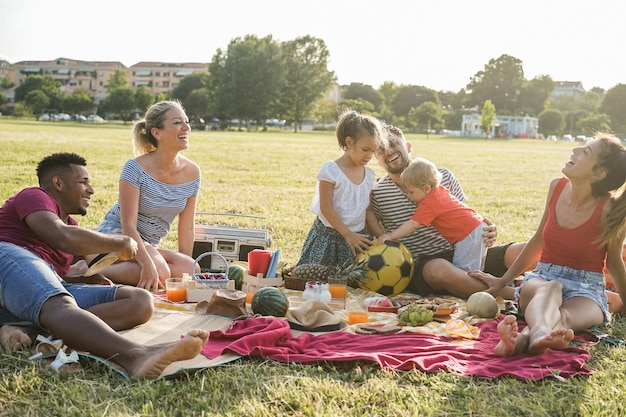 Happy multiracial families doing picnic outdoor in city park during summer vacation - main focus on african man face