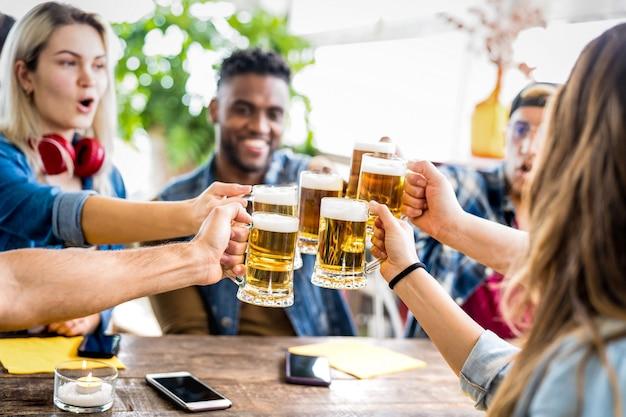 醸造所のバーでビールを飲み、乾杯する幸せな多民族の友人