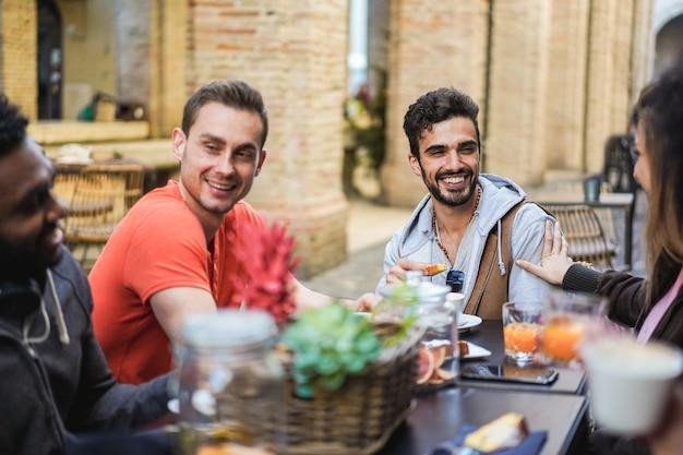 バーレストランで屋外で飲食する幸せな多民族の友人-右男の顔に主な焦点