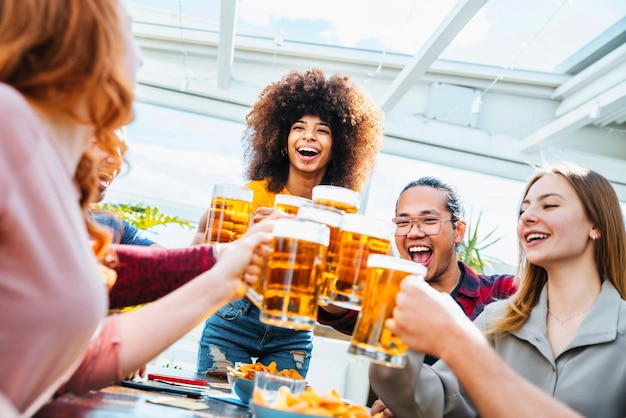 양조장 펍 레스토랑에서 맥주를 마시는 행복한 다인종 친구 그룹 -