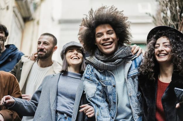 街でアウトドアを楽しんでいる幸せな多民族の友人-アフリカの男の顔に焦点を当てる