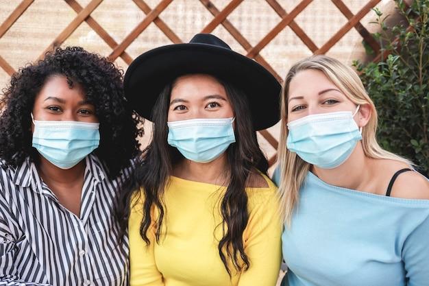 코로나 바이러스 발생 동안 야외에서 셀카를 복용하는 행복한 다민족 친구-아시아 소녀에 대한 주요 초점