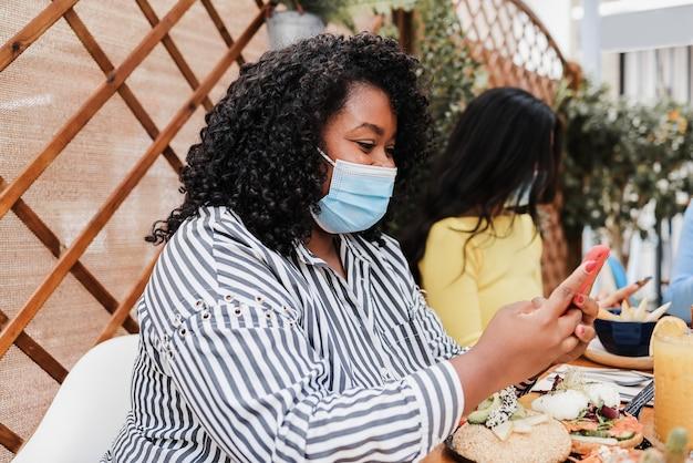 마스크를 쓰고 브런치 레스토랑에서 야외에서 휴대폰을 사용하는 행복한 다인종 친구 - 아프리카계 미국인 소녀에 초점